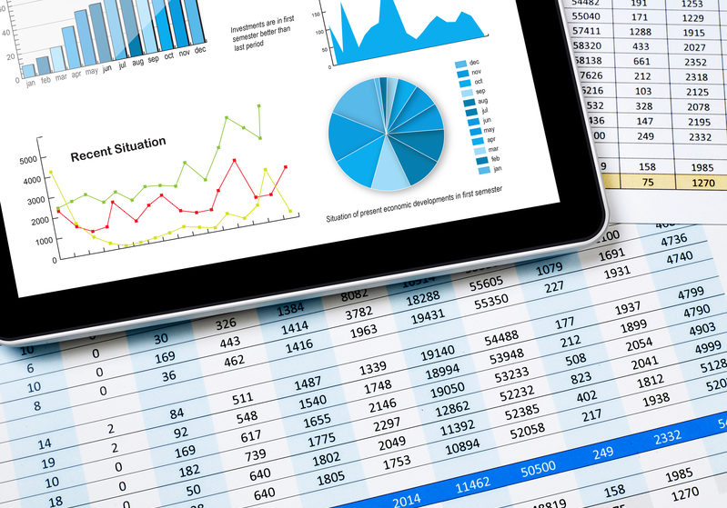 Tablet and paper with financial data